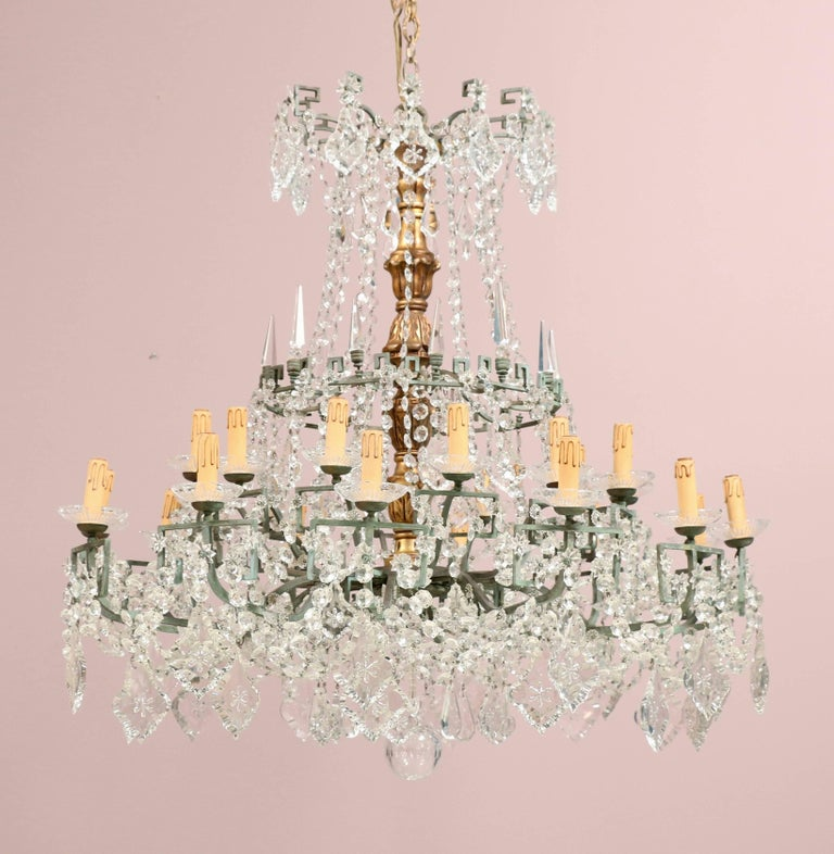 Majestic 1940s, Italian crystal, gilt-wood and bronze two-tier chandelier in the Neoclassical style. The chandelier is composed of a gilt-wood center column, a bronze frame with a Greek key motif and and an abundance of crystal beads and prisms (in