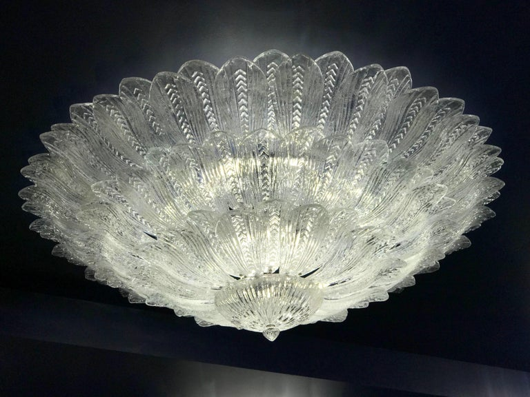 Realized in pure Murano glass, each chandelier consists of an incredible number of leaves. Gold plated frame with 18 E 27 bulbs spread a magical light. Available also a pair. By Galleria Veneziani Measures: diameter 180 cm, height 60 cm and chain