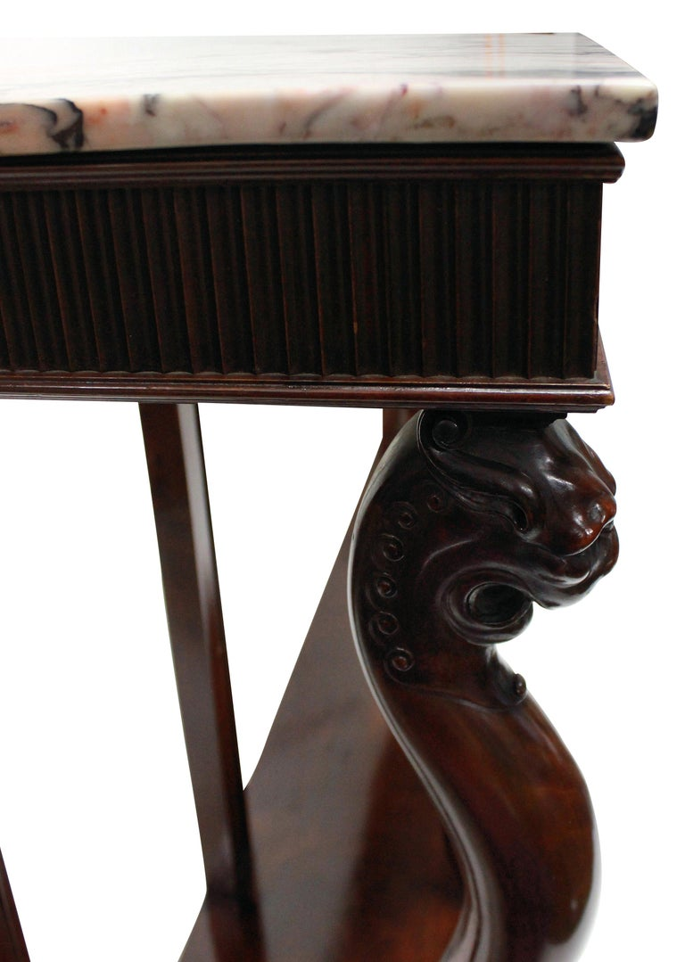An Italian console table in the neoclassical manner of monumental proportions. Beautifully carved in mahogany with a good patina. Comprising four monopodia legs, which are stylized lions, supporting a tambour front and a shaped thick breche Violette