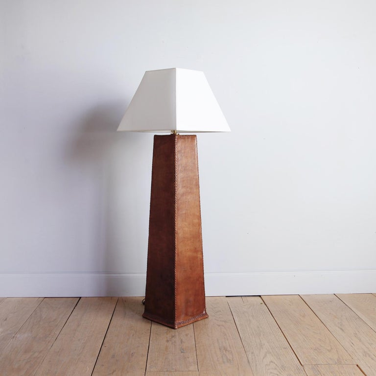 An impressive and unique, handstitched leather floor lamp, the cognac-brown leather covering a tapered columnar base. The design's appeal rests in its classical proportions and warm, mottled patina.  Dimensions include the custom parchment paper