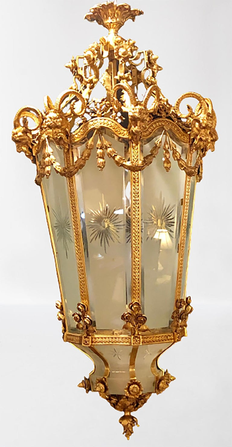 A Louis XVI style monumental Dore bronze rams head etched glass lantern. This spectacular one of a kind lantern is simply too stunning to behold. The frosted and etched star burst curved panels of glass framed in a heavy thick gilt gold bronze of