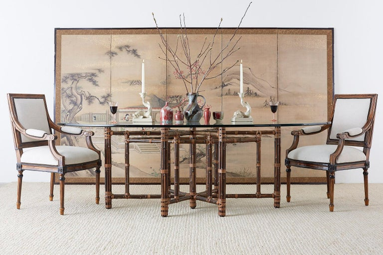 Monumental California organic modern bamboo rattan oval dining table custom made by McGuire. This bespoke dining or conference table features a 58 inch wide 28 inch deep iron hexagonal base wrapped entirely by bamboo rattan poles lashed with leather