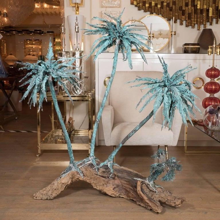Monumental metal palm tree sculpture on driftwood base.