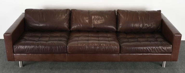 A fabulous large-scale sofa by Ralph Lauren upholstered cocoa or chocolate brown leather with tufted button cushions. This sofa has a brushed aluminum finish on steel legs. The cushions may have been reupholstered in faux leather at some point.