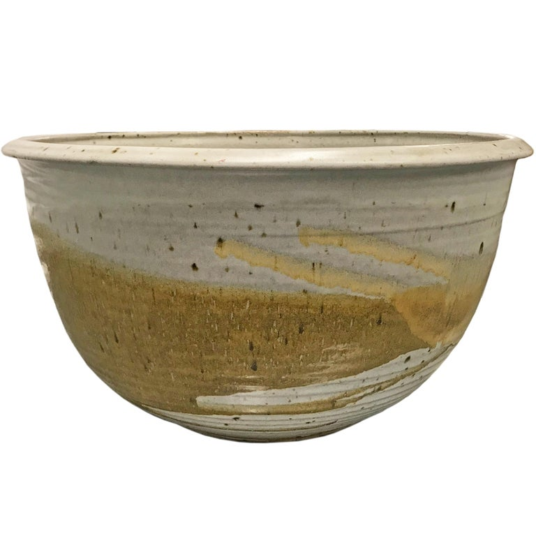 A monumental-scale mid-20th century American studio hand-thrown glazed ceramic bowl with fantastic texture and earthy neutral glaze colors. Signed illegibly on the bottom.