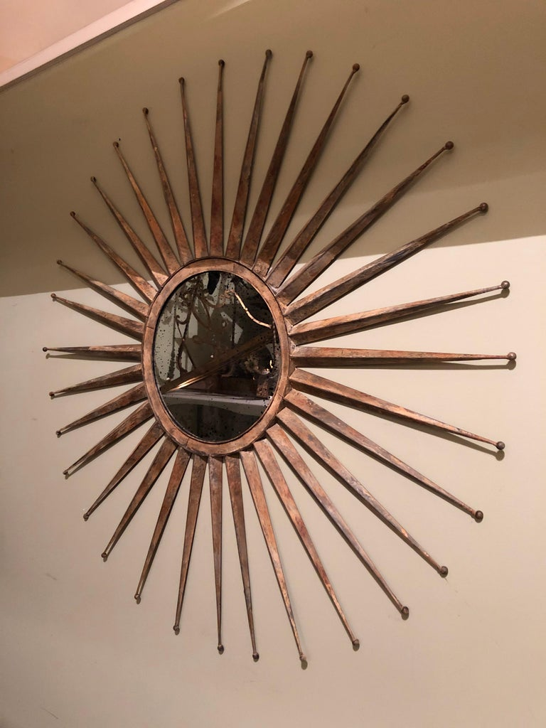Monumental Mid Century rustic metal starburst mirror. Mirror has black speckled antiqued look to it. Starburst ends have little balls at the end. Actual mirror diameter itself is 13