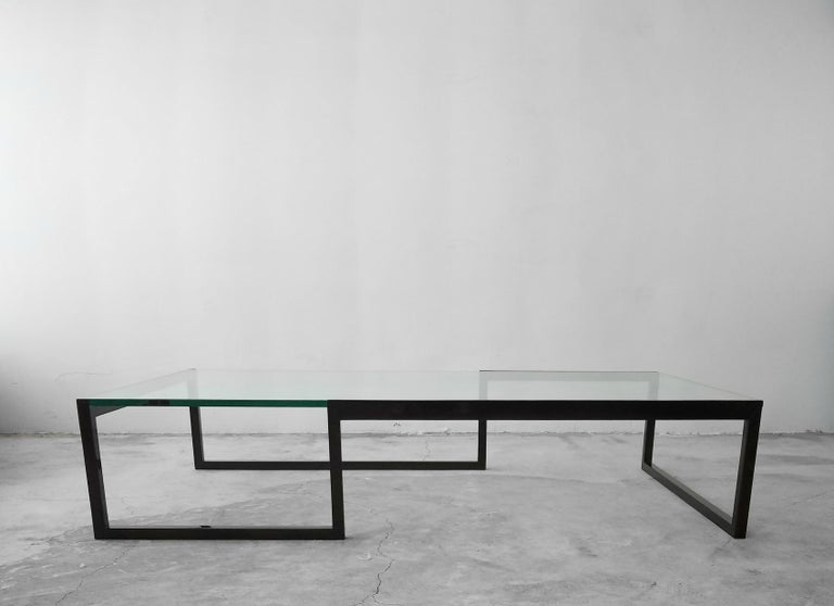 This is an extremely large and versatile metal and glass coffee table. The table frame is a unique shape and very minimal and modern in appearance. The frame has been lacquered, and under the lacquer is a wood grain, so it's a metal table that looks