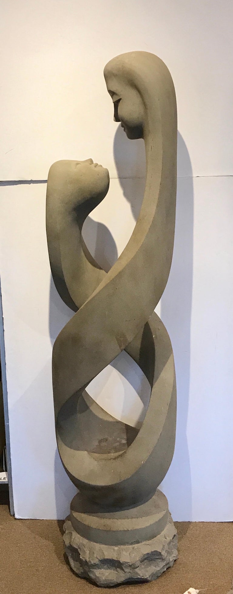Monumental modern carved limestone spiral sculpture, with two figural heads facing each other. Standing 76