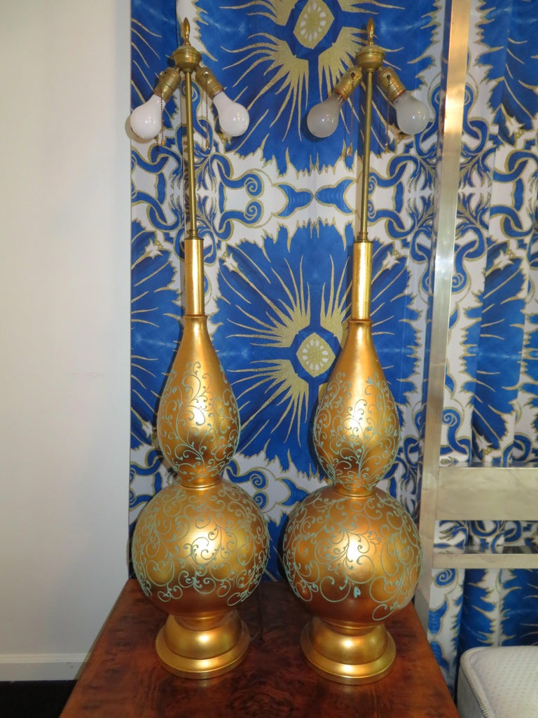 Monumental and magnificent pair of gold leaf gourd shaped lamps with their original golden shades. There are no words to describe how absolutely fabulous these lamps truly are. They are a whopping 52