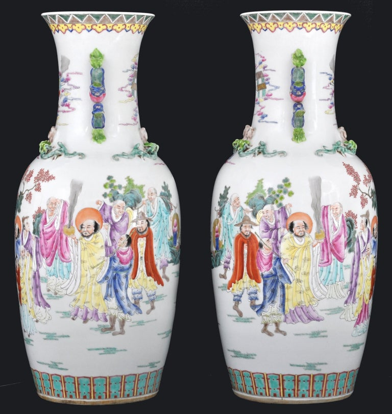Monumental pair of antique Chinese late Qing to early Republican period Famille Rose Porcelain vases. The vases of baluster form with applied handles modeled as dragons, each vase with a hand painted polychrome scene of immortal figures in a garden