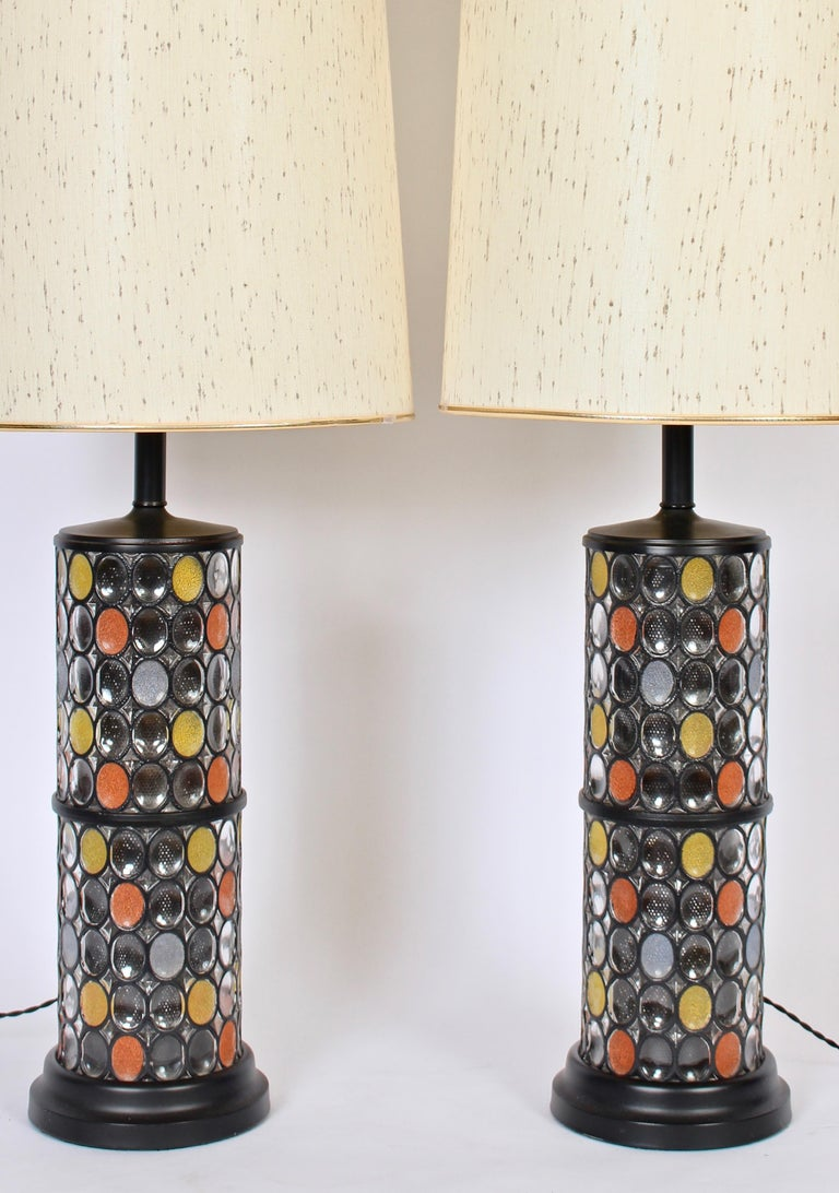 Substantial pair of black enameled metal and fused glass illuminating table lamps in the manner of Higgins glass studio. 3' H. Featuring a lantern form with interior cylindrical black screen insert. Surround detailed with clear and ovoid granulated