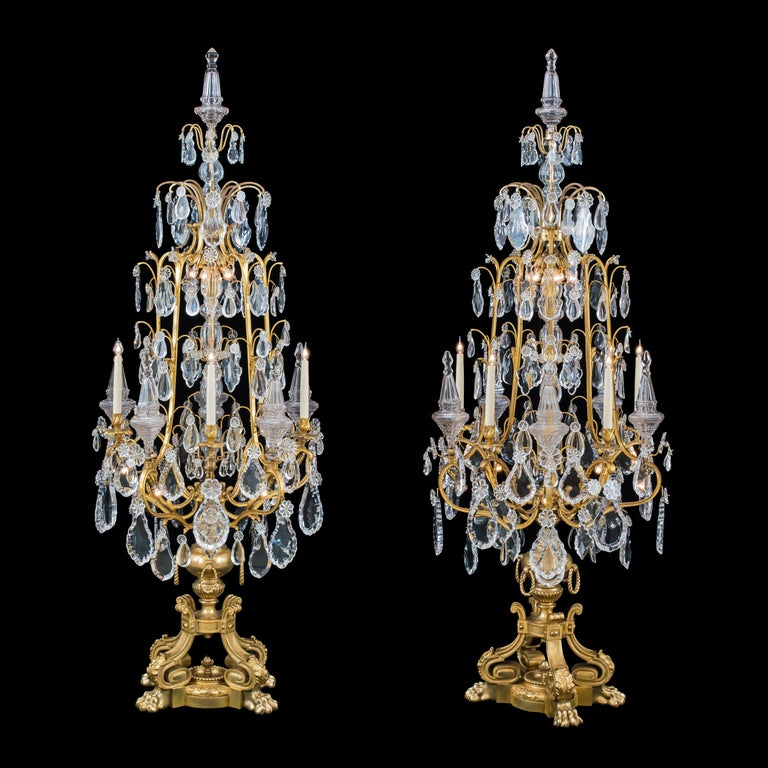 A magnificent pair of Louis XV style Ormolu and crystal girandoles Probably by Baccarat  Constructed from finely cast and chased ormolu, the imposing floor candelabra—almost 2-meters tall—are supported on four lion's paw feet surrounding a