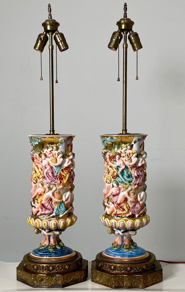 """Large and uncommon Capodimonte. Produced between 1920 and 1950. Each lamp measures 35"""" tall, 9"""" wide and 8"""" deep. The ceramic porcelain component are each 16"""" tall, 6"""" deep and 7"""" wide. A rare pair to have. Each piece has a slightly different hand"""