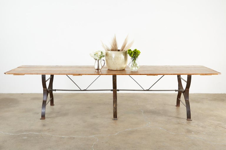 Monumental harvest table or farmhouse dining table featuring a triple leg cast iron trestle base measuring nearly 11 feet long with a rustic pine plank top. The cast iron Curule leg bases are conjoined by a long cross stretcher having a decorative