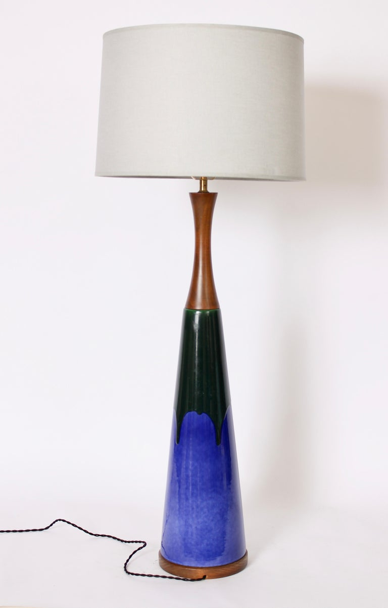 Majestic Raymor Imports glazed bright blue and dark green ceramic and walnut 44 H Lamp. Featuring a slim ceramic cone form in high gloss blue with deep Emerald green drip glaze. with slender walnut neck. Slender. Colorful. Small footprint. 44 H to
