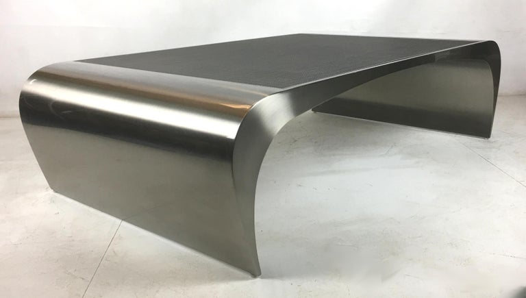 Sculptural stainless steel Tour de Force by Brueton. The materials and workmanship are nothing short of stunning quality. The seamlessly welded and lightly brushed finish stainless steel body and the inset stainless steel grid top work together to