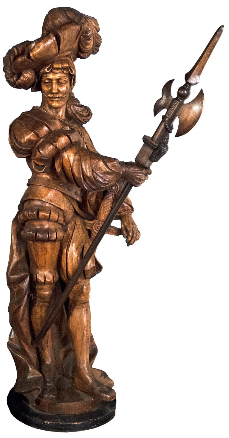 A larger-than-life sculpture of a Pontifical Swiss Guard made of solid carved walnut. The Swiss Guard are the official security for the Pope since 1506. To this day, they still wear this uniform, which were designed by the artist Michelangelo.