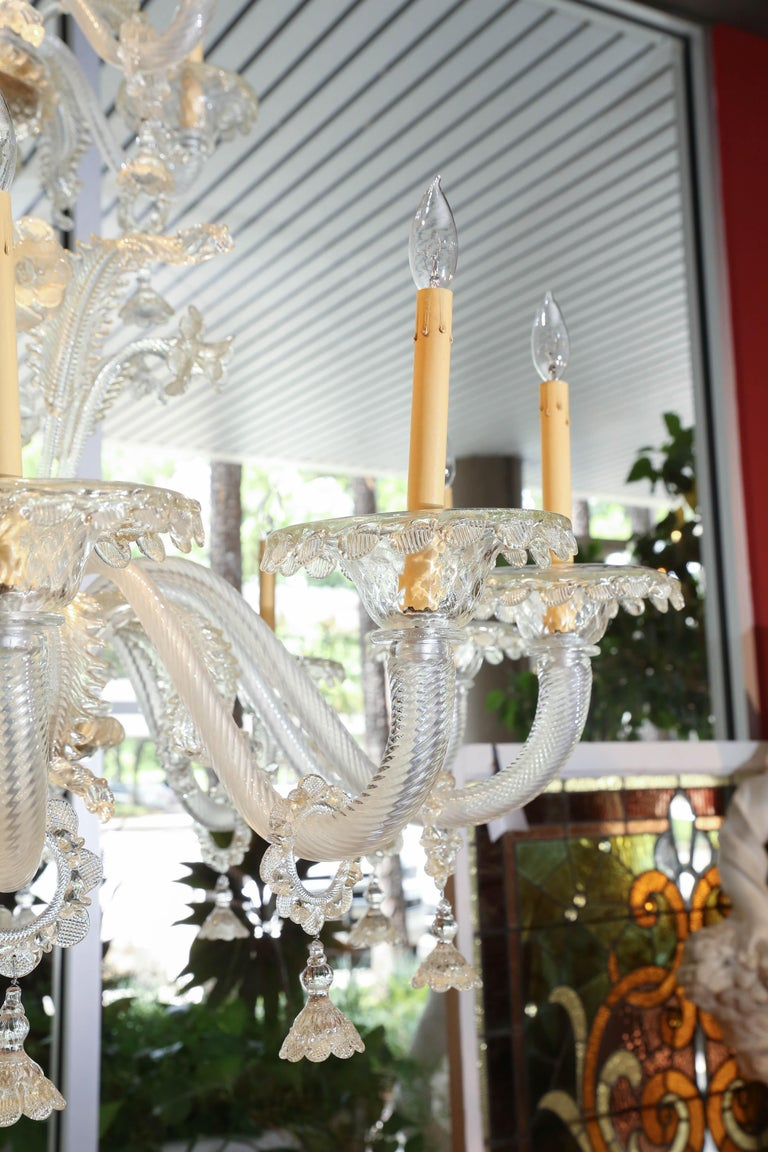 Large-scale Venetian glass chandelier with 18 lights. This chandelier is an exquisite shade of pale gold Lovely glass bells hang from each arm. Glass foliate and floral stems decorate this piece.