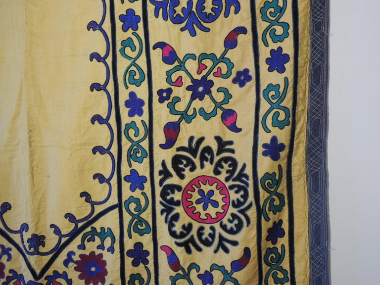 Monumental vintage yellow and green embroidery Suzani panel with quilted trim all around. Backed with floral cotton print fabric. In shades of green, royal blue, yellow, pink, orange, blue, black. Ideal to hang on a wall or as a bedspread. Size: