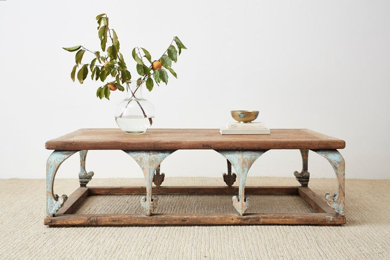 Monumental rectangular coffee or cocktail table having a rustic, weathered patina. Constructed from reclaimed pine featuring arched legs with a spade foot motif. The supports have a distressed polychrome finish with lacquer paint remnants. The aged