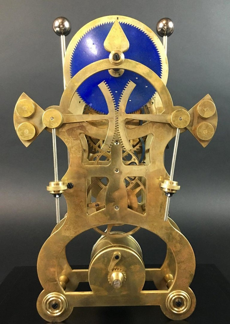 Moon dial grasshopper clock following John Harrison  A grasshopper clock following John Harrison, brass skeleton clock, 2 dials in white enamel, 2 counter-directional rod pendulums, steel rope winding on winch. Solid wooden plinth, loose glass
