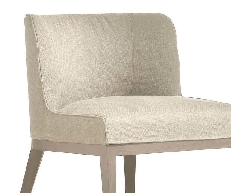 Sophisticated and elegantly-proportioned, this chair features an ash base with bleached finish that blends elegantly with the white fabric upholstery (col. 1310/01 cat. H). Chaneling a bold mid-century modern style, this head-turning design is
