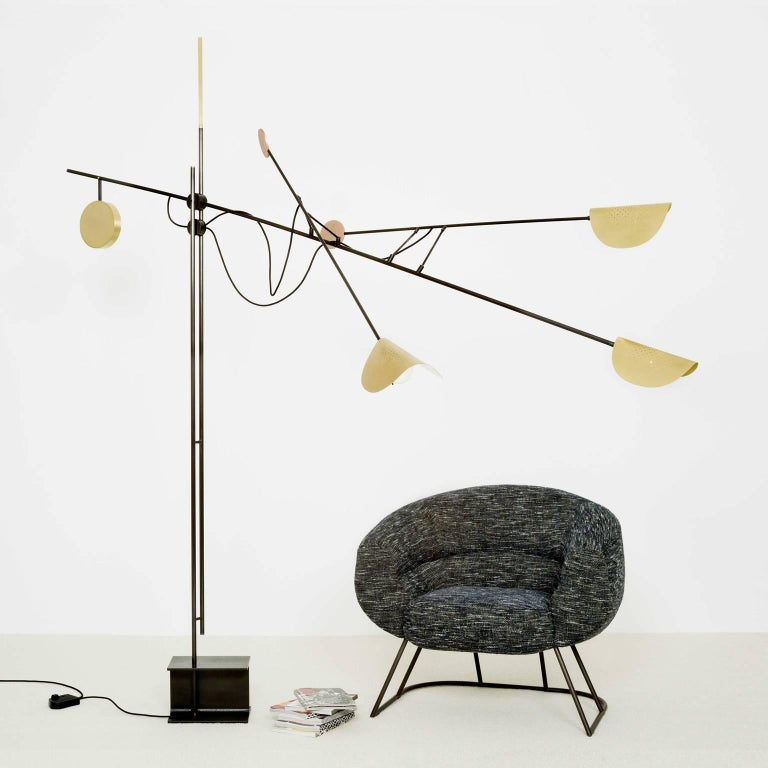 This floor lamp evokes a metallic industrial architecture by its silhouette. The Moon moves in balance in space and refines itself until its ends which confers to him luminous and colored points of reflections.  Materials: - Iron with hematite
