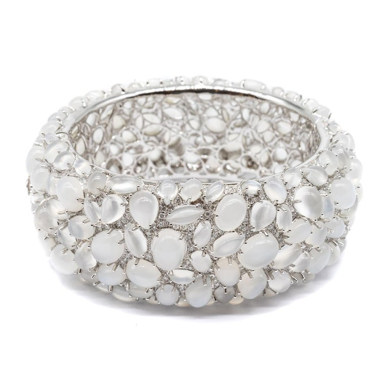 A moonstone and diamond bangle bracelet, set with cabochon-cut moonstones, weighing an estimated total of 138.45ct, and pavé set round brilliant-cut diamonds, weighing an estimated total of 4.84ct, mounted in 18ct white gold.