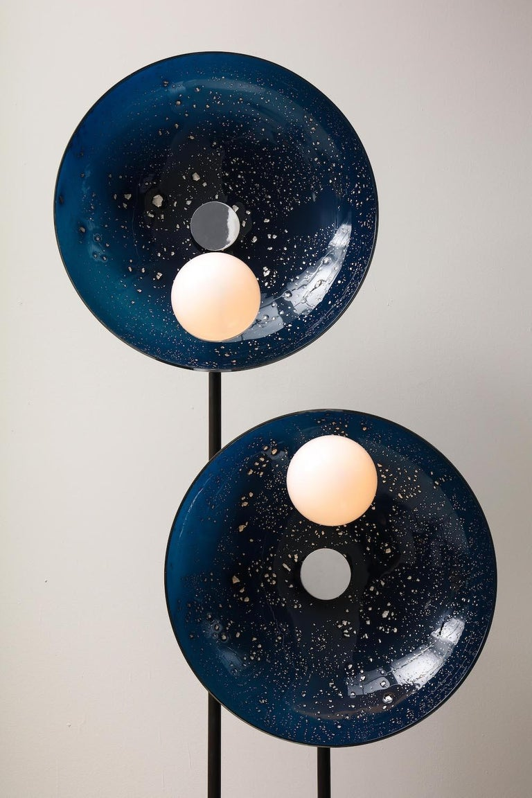 Two shallow glass bowls in ultramarine blue, with applied platinum foil, and two glass-globe shades. Each globe is half opaque-white and half clear. All glass is hand-blown by the artist. Black-patinated bent brass arm with chrome-plated mounts.