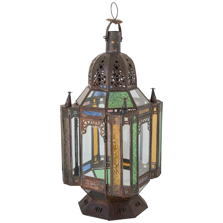 Handcrafted vintage Moroccan metal glass lantern or Moorish pendant. Moorish style North African lantern with multi-color molded colored glass panels in green, lavender, blue and clear. Hurricane candle lamp handmade in Marrakech, vintage metal in