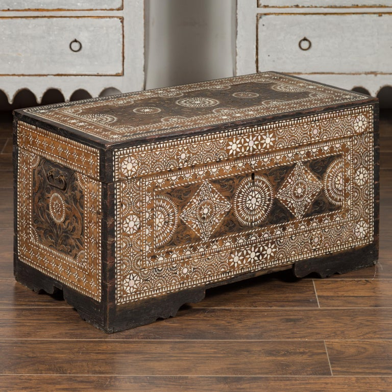 A Syrian Moorish style blanket chest from the early 20th century, with geometric mother of pearl inlay. Born during the first quarter of the 20th century, this blanket chest features a linear silhouette, perfectly decorated with an abundance of