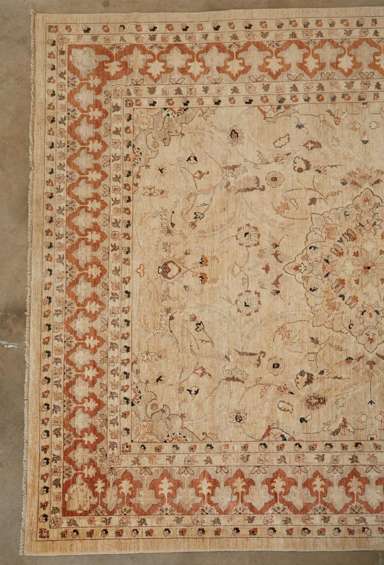 Distinctive vintage hand knotted wool Turkish Oushak rug. Large rug with a beige field having a medallion encircled by free form floral and vines. The border features an arabesque or Moorish style fleur-de-lis shaped reverse design in a burnt sienna