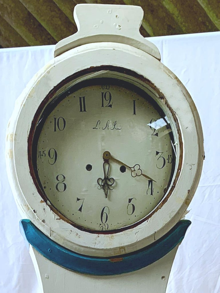 Swedish country Mora clock from early 1800s in white paint finish and blue detail with a Classic shape body and a good face with lots of detail and nicely detailed hood in good condition. Measures: 204cm.  It has the Classic extended belly of a