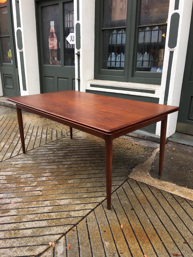 Moreddi teak dining table with 2 pull out / pull-out leaves. Table retains its original finish and is in great shape! Shows minimal surface scratches. Pull out / pull-out leaves are slightly lighter in color from being stored away most of the time!