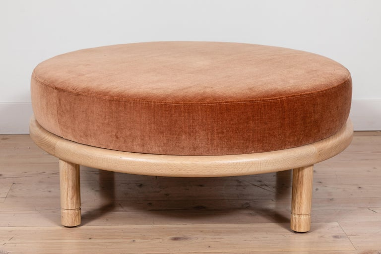 The Moreno Ottoman features a round solid wood base with four cylindrical legs and an upholstered top. Available in American walnut or white oak. Shown here in natural oak.  Available to order in customer's own material with a 6-8 week lead