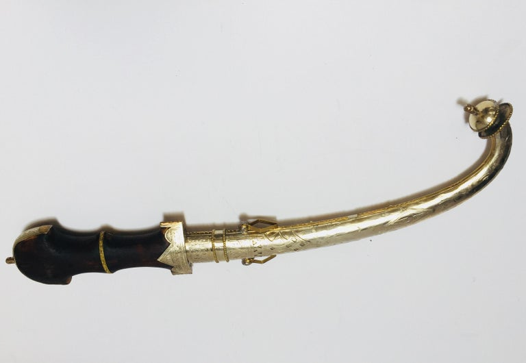 Moroccan Arabian koumaya or Jambiya, which is the name for the Arabic dagger. Ornate with brass and silvered steel hammered element and wood handle. The dagger is very large and it is curved with a thick double edge blade, the handle is ornate