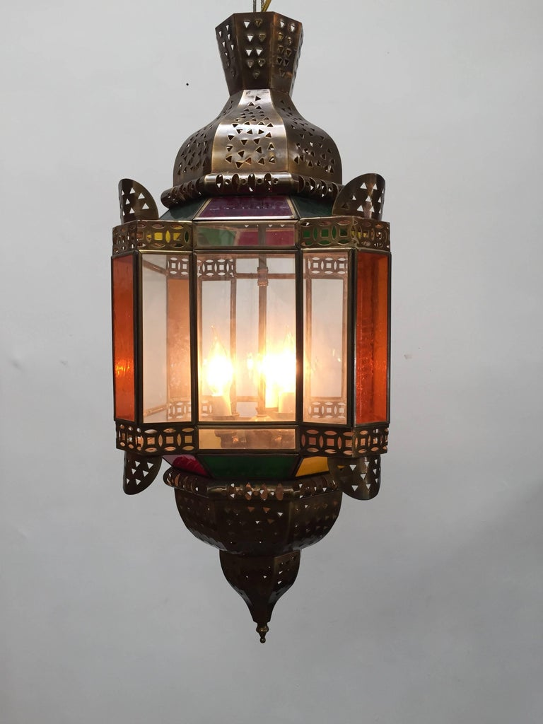 Handcrafted Moroccan light fixture with clear and colored glass. Moorish style glass pendant with colored glass in green, red, yellow and amber with filigree brass metal designs. This Moroccan light fixture is rewired for three lights.