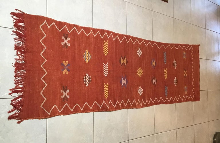 Beautiful handwoven rug made of cactus silk with soft multi-color geometric motifs on a red - salmon color background, nicely feel to touch. Great decorative addition for any room.