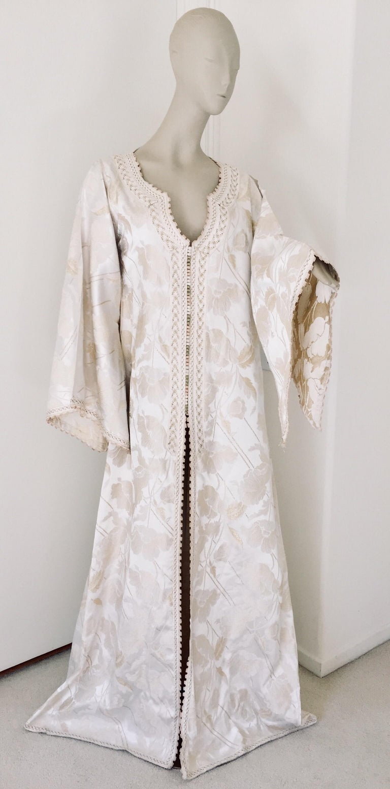 Elegant Moroccan white ivory and old brocade kaftan embroidered with gold trim threads. Size L to XL circa 1980s. This long maxi dress kaftan is embroidered and embellished entirely by hand. One of a kind evening Moroccan Middle Eastern