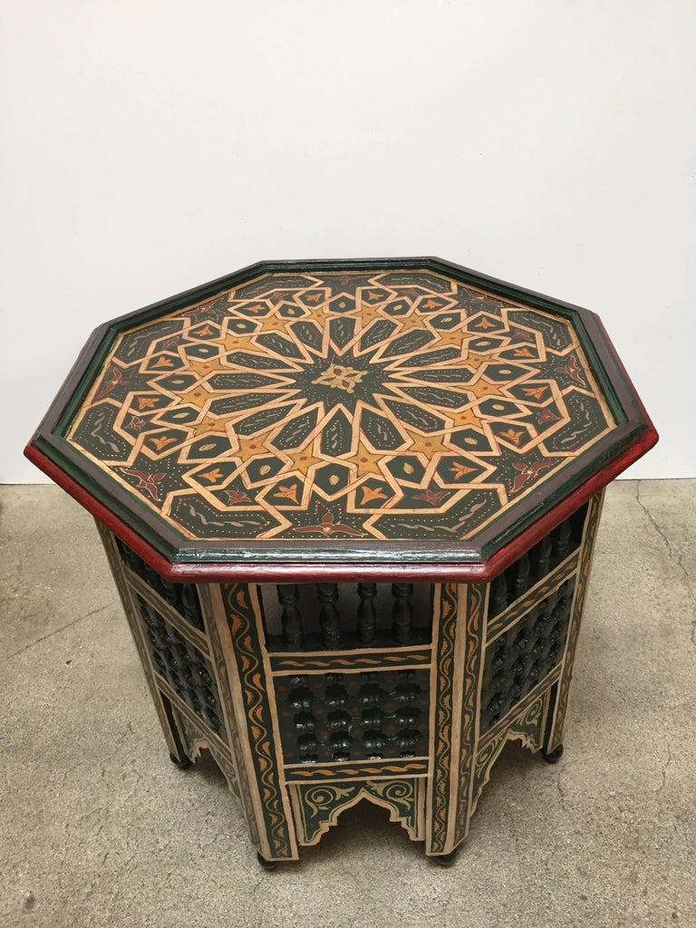 Moroccan colorful hand-painted dark green side table with Moorish design and open fret mousharabie work on sides. Dark green background with multicolored floral top and geometric designs. Very fine wood artwork on an octagonal shape with Moorish