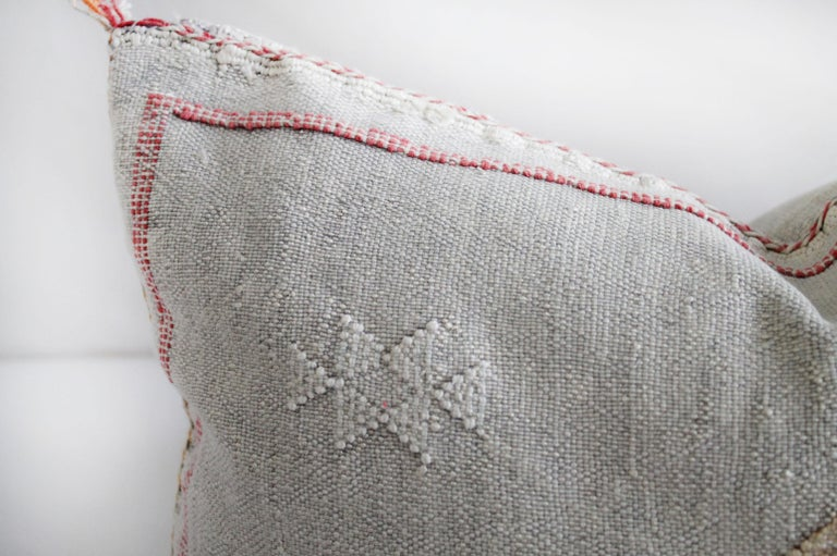 Moroccan handwoven cactus silk pillow As shown with a beautiful light gray tone background, and white, with reddish pink and gold accents. Hidden zipper closure, backside is the same plain cactus silk with no embroidery. Measures: 16? x 21? Does