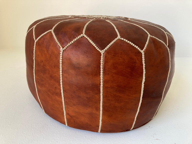 Moroccan handcrafted brown camel leather ottoman, with embroideries. Could be used a foot stool, or side table or ottoman. The Moroccan leather poufs are hand-tooled and embroidered with white tread. Very nice handmade Moroccan tan camel color