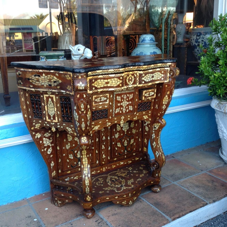 Dramatic style and flair to this ornately inlaid and unusual console fitted with  a large top drawer and 2 smaller drawers. The open carving is ornate.