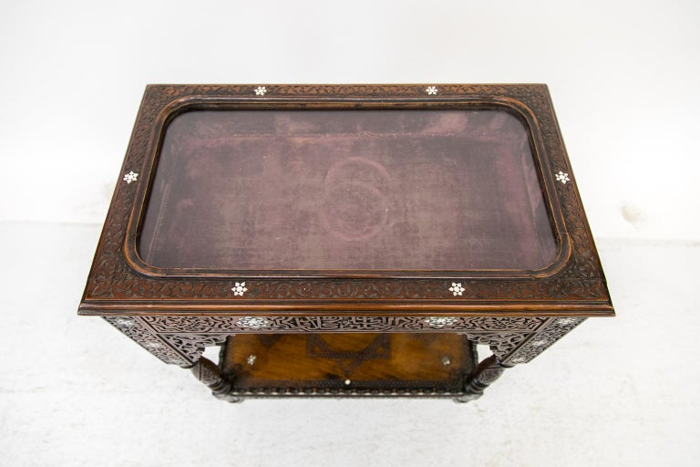 This vitrine table is carved overall with arabesques and geometric designs, and is inlaid with mother of pearl and stylized flowers. The interior display area is lined with padded burgundy baize fabric. There is a lower shelf that is carved and