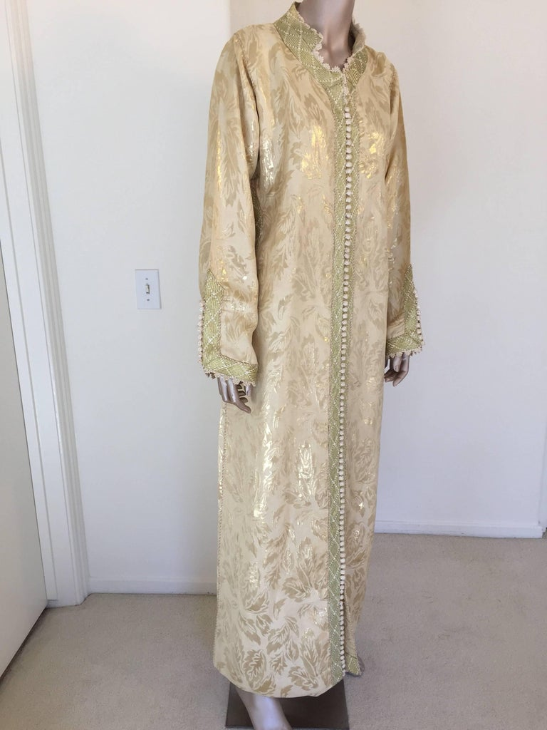 Metallic gold brocade maxi dress kaftan handmade by Moroccan artist. Handmade vintage exotic 1970s gold metallic brocade ceremonial caftan gown from North Africa, Morocco. The luminous brocade fabric shimmers with allover golden shine. This maxi