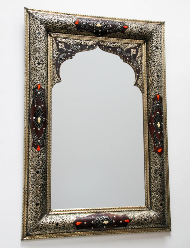 Elegant Moroccan mirror decorated with silvered repousse metal delicately engraved and wrapped with leather and amber color stones. The inside mirror has a Moorish arch in leather and fine filigree silver décor. Handcrafted rectangular Orientalist