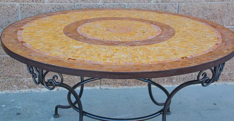A inlaid round stone Moroccan mosaic tile tabletop on a wrought iron base. Handcrafted in Morocco could be use indoor or outdoor. Spanish Moorish garden dining mosaic table in the style of Bill Willis Marrakech. The top is not attached to the