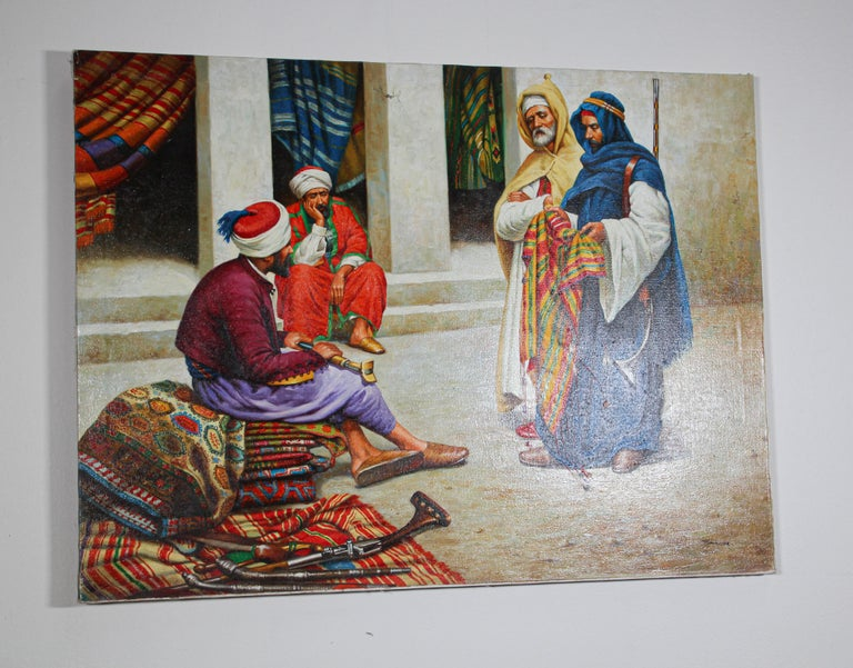 Moroccan orientalist oil on canvas painting of a 19th century Moroccan rug market scene with an sellers seating on a pile of carpet and two other men wearing traditional colorful robes standing and checking the goods. The background depict an old