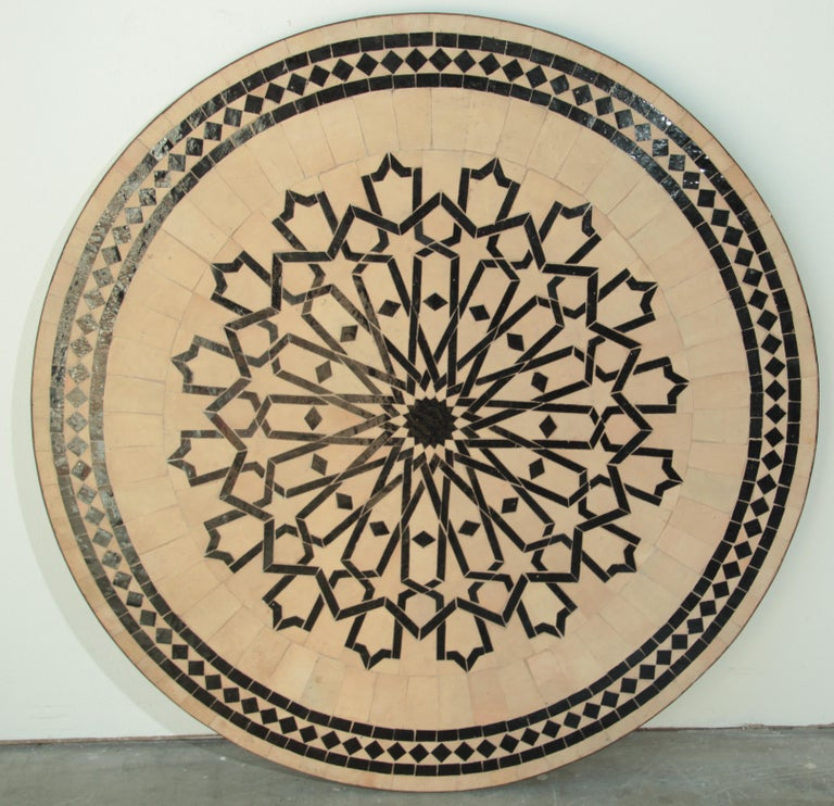 Handcrafted round Moroccan outdoor mosaic tile table 47 in. diameter on iron base. Classic and elegant Moroccan outdoor mosaic tile table sit on a black wrought iron base. Handmade in Morocco, the artisans from Fez used the Classic Moroccan cut