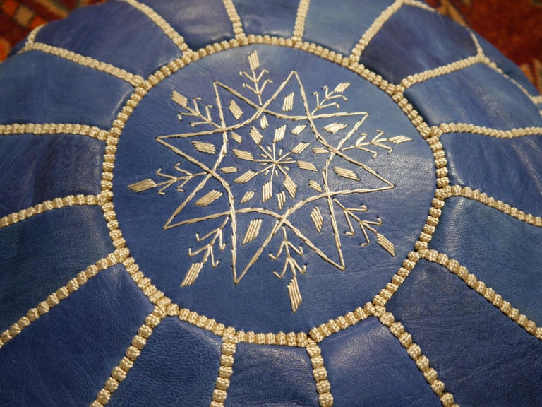A beautiful handcrafted Moroccan blue leather ottoman pouf   Construction This pouf was handcrafted by Morrocan Artisians. It consists of high quality leather with embroideries and tribal motive on top. This Item will be delivered stuffed with